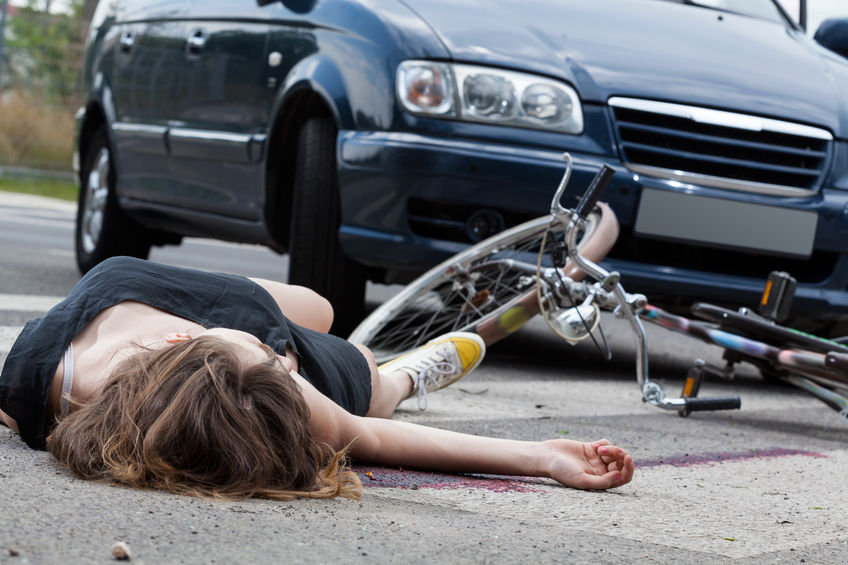 31237133 - unconscious female cyclist lying on street after road accident